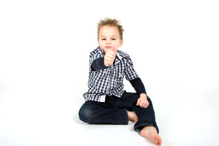 A young boy is holding his thumb up. photo