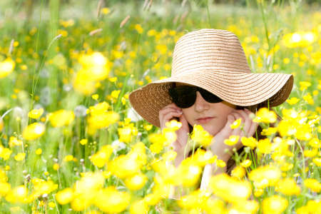 enyoing: A young girl is enyoing the sun and nature.