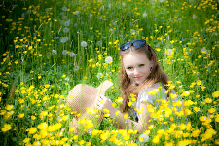 Young girl is sitting in a field of grass and flowers. photo
