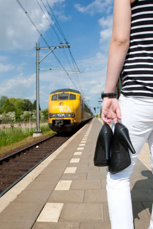 Waiting for the train with the shoes in her hand.