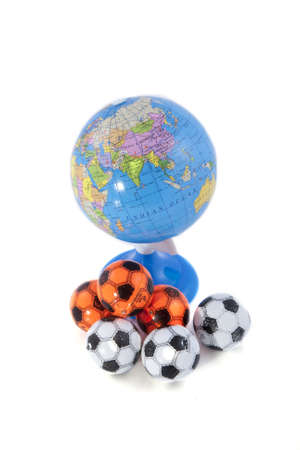 A globe and some footballs on a white background. Stock Photo - 7102245
