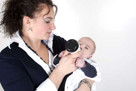 A mother is feeding her child on a white background.