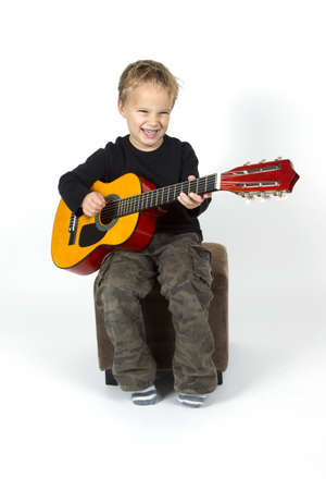 Young boy is playing on the guitar.