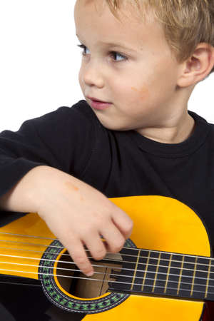 Young boy is playing on the guitar on a white background. photo