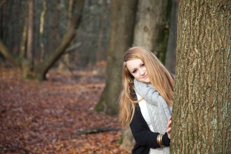 Young girl is hiding behind a tree photo