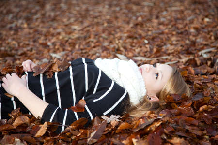 Young girl is resting in a bed of leaves in the forest photo