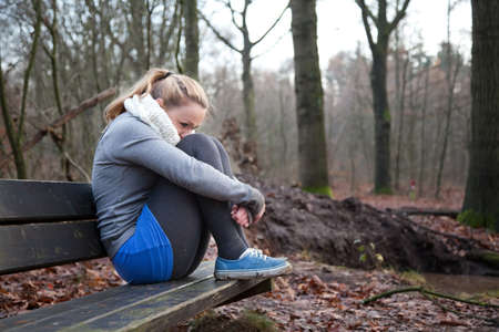 Young girl is sitting depressed on a bench.