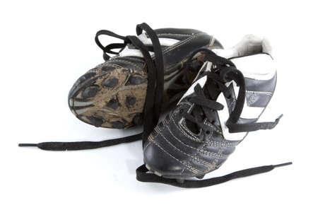 pieds sales: Chaussures de football boueux sur un fond blanc.