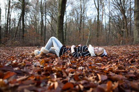 Young girl lying in the leaves in the forrest photo