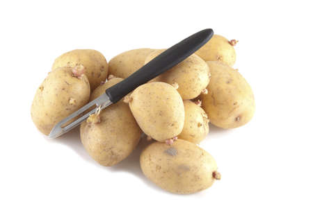 Potatoes with a peeler on a white background. Stock Photo
