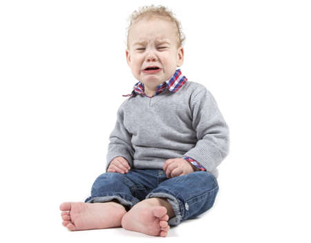 Young baby boy is crying on a white background. Stock Photo