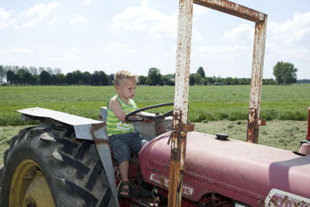 Young boy is driving a farm vehicle in the open. photo