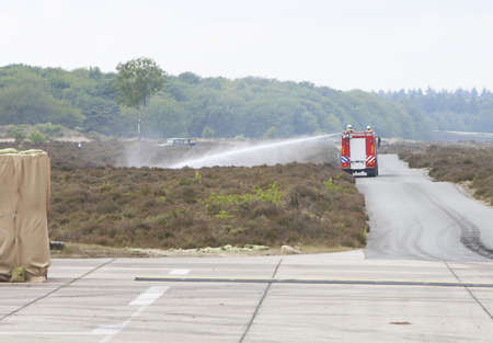 A fire truck in action in the open field.