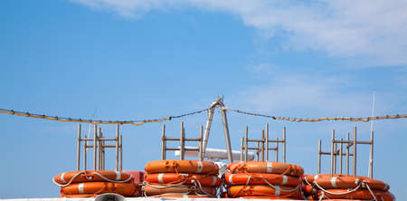 Piled lifejackets with a blue sky. Stock Photo