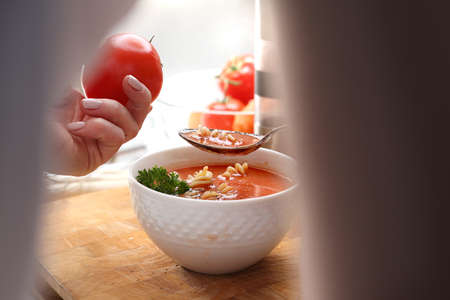 The woman is eating a tomato soup. A small hot, appetizing home-made tomato soup with the addition of pasta. 版權商用圖片