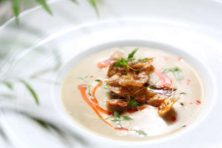 An exquisite, delicate cream soup served with crunchy crisps from baked potatoes. Horizontal shot 版權商用圖片