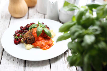 Cauliflower cutlets served with roasted peppers sauce on dumplings on gnocchi, roasted beetroot salad. Reklamní fotografie