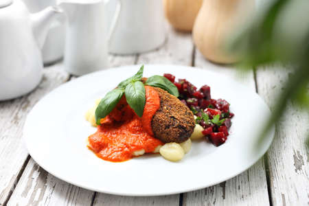 Vegetable cutlets served with tomato sauce on dumplings on gnocchi, roasted beetroot salad.