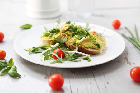 Appetizing sandwiches with egg paste and chives served with salad and tomatoes. Horizontal frame.