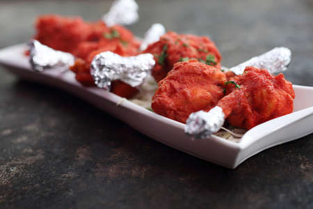 Appetizing spicy dish. Red chicken baked in a colorful marinade.
