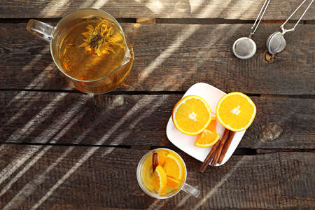 Green tea. A jug of green aromatic tea with the addition of orange and cinnamon on a wooden natural counter. horizontal composition, top view