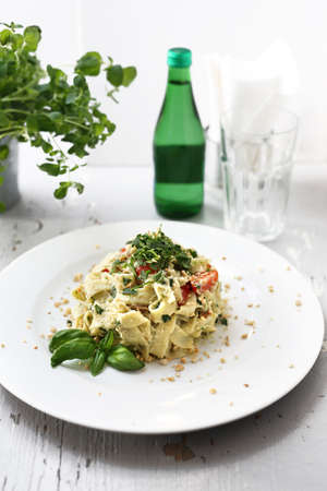 Appetizing vegetarian lunch, pasta with vegetables served with a bottle of water. Horizontal composition.