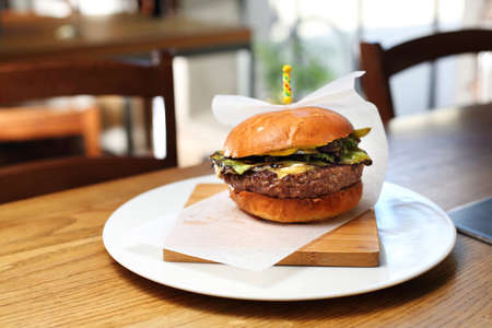 Appetizing beef burger with green vegetables served on a wooden board. Proposal proposal, menu. Horizontal composition