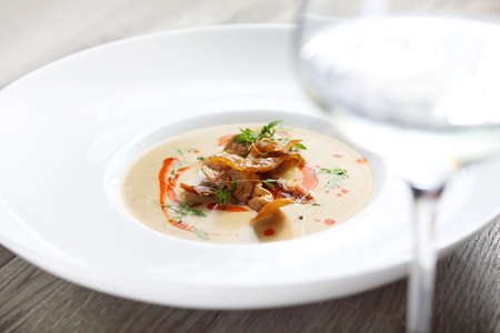 An exquisite, delicate cream soup served with crunchy potato chips and a glass of white wine. Horizontal shot
