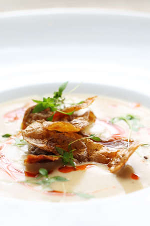 An exquisite, delicate cream soup served with crunchy crisps from baked potatoes. Vertical shot