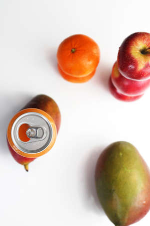 A can of fresh squeezed tropical fruit juice on a white background. Mango fruits, mandarins, oranges, apples. Top view