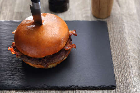 Burger with bacon. Grilled beef cutlet in a bun. Stock Photo