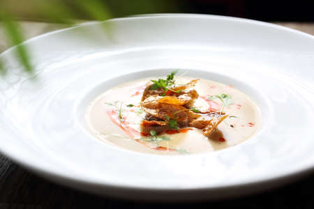 An exquisite, delicate cream soup served with crunchy crisps from baked potatoes. Horizontal shot Imagens