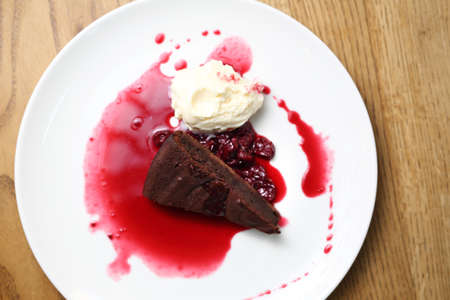 Tasty chocolate cake with hot raspberry sauce and ice cream. Horizontal composition