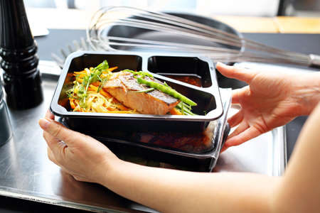 Hand holding a Catering Box. Takeaway food in a box. Banco de Imagens