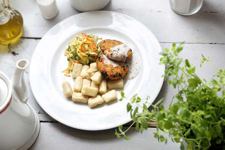 Vegetable cutlet with yogurt and herb sauce served with potato dumplings and coleslaw and carrot salad. Dish on a white plate. Horizontal composition Banco de Imagens