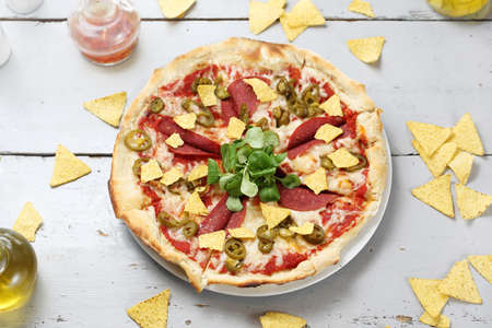 Pizza with cheese, soy salami, jalapeno pepper, arugula on a thin gluten-free dough made of corn flour served with crispy nachos. Top view