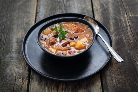 Soup in a black plate on a wooden background.