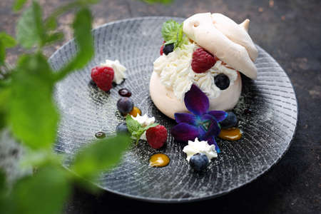 Sweet dessert. A meringue cake with whipped cream and mascarpone with seasonal fruits served on a black plate 스톡 콘텐츠