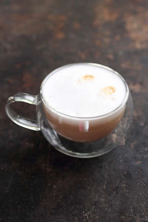 Hot, aromatic coffee with milk. Drink on a dark background.