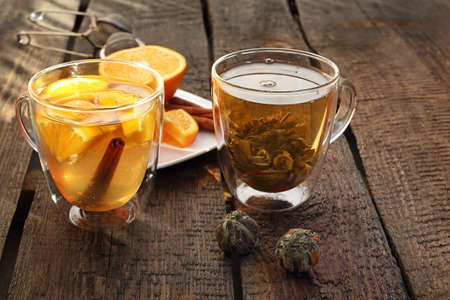 Tea. A glass of green aromatic tea with the addition of orange and cinnamon on a wooden natural counter. horizontal composition