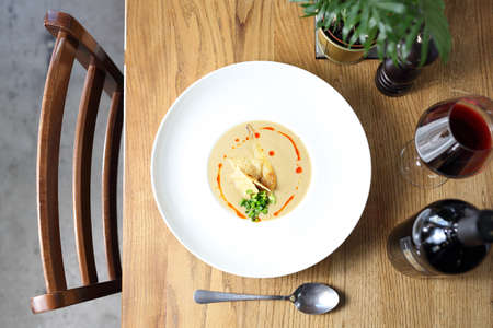 Tasty, appetizing soup served in a white plate on a wooden table. Proposal proposal, menu. Horizontal composition. Top view 스톡 콘텐츠