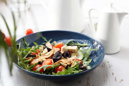 A plate of appetizing healthy, vegetarian lettuce on a white table.