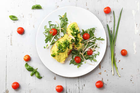 Appetizing sandwiches with egg paste and chives served with salad and tomatoes. Horizontal frame, top view Stockfoto