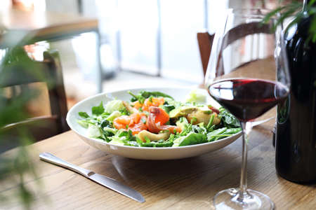 Tasty, appetizing healthy salad by white plate on a wooden table. Proposal proposal, menu. Horizontal composition