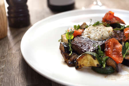 Grilled steak of entrecote with herb butter and grilled vegetables served on a white plate.