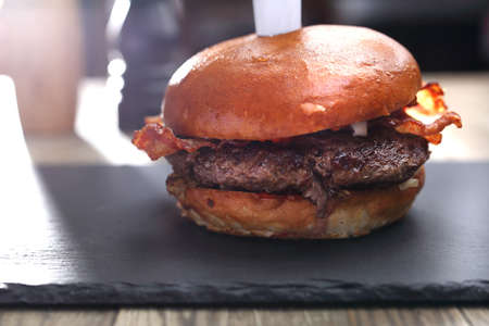 Beef burger with roasted bacon and ketchup. Served on a black plate pierced with a knife