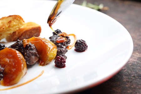 Stylization of dishes .Fried chicken liver with raspberry and blackberry fruit served with caramelized apple and croutons