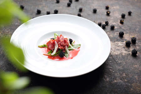 Beef carpaccio served on raspberry and blackberry mousse. Appetizer