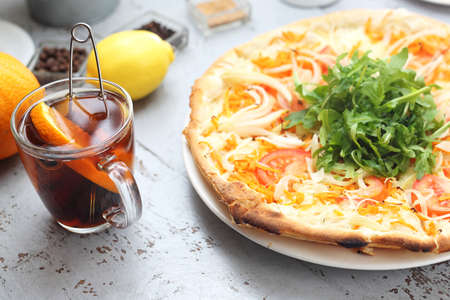 Traditional Italian thin crust pizza. Appetizing dish on a white countertop in a composition with kitchen accessories. Zdjęcie Seryjne
