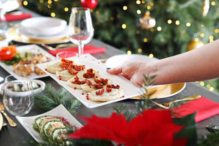 Dumplings with cabbage and mushrooms. Christmas dinner Christmas dinner, woman serves traditional Christmas dishes at the table.